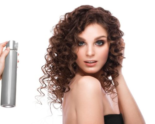 Beautiful brunette girl with a perfectly curly hair with spray bottle, and classic make-up. Beauty face. Picture taken in the studio on white background.